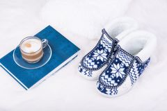 Pair of warm female slippers, milk coffee and blue book on white furry carpet.  Royalty Free Stock Photo