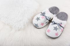 Pair of warm female slippers on white furry carpet Royalty Free Stock Image