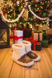 Pair of warm home shoes made of wool stands near the Christmas tree with gifts at home on the wooden floor Royalty Free Stock Image