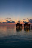 Pair of water villas at dawn Maldives. Indian Ocean Mar-28-09 sunrise over the tranquil water reflections Royalty Free Stock Images