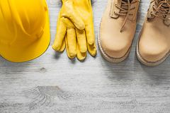 Pair of waterproof boots hard hat leather safety gloves on woode Stock Images