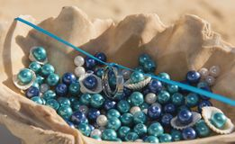 Pair of wedding bands hung on ribbon in seashell. Pair of white gold wedding bands rings hung on blue ribbon in seashell romantic tropical beach ceremony stock photography