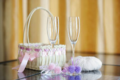 A pair of wedding glasses and a ring pillow Royalty Free Stock Photos