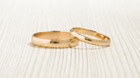 Pair of wedding golden rings on the bright wood background Royalty Free Stock Photography