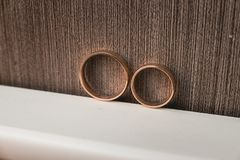 Pair of wedding golden rings on a brown wall background. Yellow toned Stock Photo