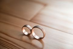 Pair of wedding golden rings on the yellow wooden floor. Selective focus Stock Images