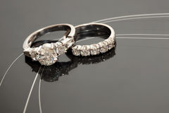 Pair Of Wedding Rings. A pair of wedding rings on a reflective grey surface