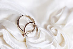 Pair of wedding rings. On a white fabric Royalty Free Stock Photos