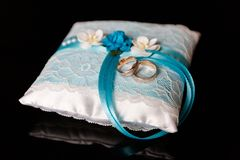 A pair of wedding rings on a blue pillow stock photography