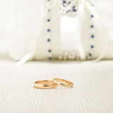 Pair of wedding rings in front of luxury cushion Stock Images