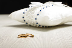 Pair of wedding rings in front of luxury cushion on the floor Stock Images