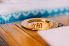 Pair of wedding rings on a golden salver with traditional slavic ornamented cloth at background Royalty Free Stock Photography