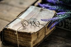 A pair of wedding rings on a old antique vintage book. With lavender stock image