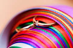 Pair of wedding rings in stack of rainbow colored ribbons. Royalty Free Stock Photo
