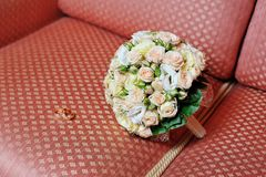 Pair of wedding rings and wedding bouquet on sofa Stock Images