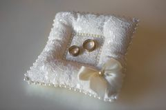 A pair of wedding rings on a white pillow royalty free stock image