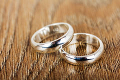 Pair of wedding rings on a wooden background Stock Photo
