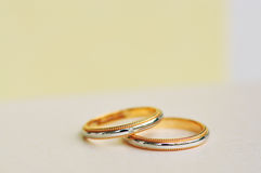 A Pair of Wedding Rings with a yellow background Stock Photography