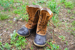 Pair of wet hunting boots on glade in forest. At sun autumn day Stock Photos