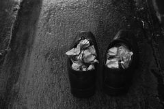 A pair of wet shoes in a rainy day. A pair of wet shoes with folded newspaper inside in the rainy day in black and white stock images