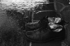 A pair of wet shoes in a rainy day. A pair of wet shoes with folded newspaper inside in the rainy day stock photos