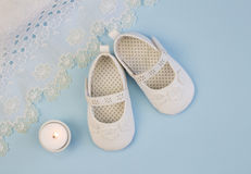 Pair of white baby booties on blue background with lace christen. Pair of white baby booties on blue background with lace  dress Stock Photography