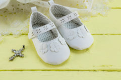 Pair of white baby booties on yellow table with lace dress Stock Images