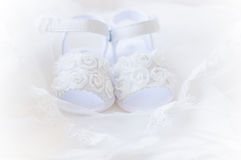 Pair of white baby shoes , christening white dress. Pair of white baby shoes on embroidered christening white dress Stock Photos