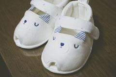 A pair of white baby shoes on wooden table royalty free stock photos