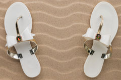 Pair of white beach sandals in rhinestones stand on the sand. Stock Photos