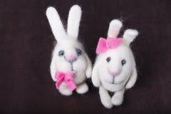 Pair of white decorative bunnies. A pair of white decorative bunnies with pink bows Royalty Free Stock Photos