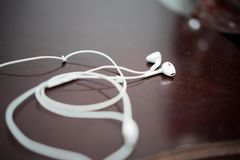 White earphone on the wooden table stock photo