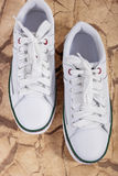Pair of White Fashionable Laced Trainers On Wooden Surface. Stock Images
