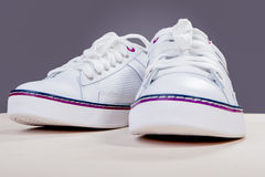Pair of White Fashionable Leather Trainers on Wooden Surface Aga Stock Images