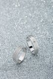 Pair of white gold wedding rings with diamonds on sparkle background. Silver rings with gemstones. Romantic fashion jewelry advertising royalty free stock photo