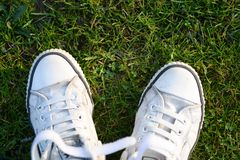 Pair of White Lace-up Sneakers on Top Green Grass Royalty Free Stock Images