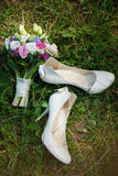 Pair of white ladies shoes on grass and beautiful bouquet of flo Stock Image