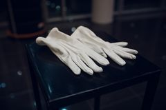 A pair of white leather gloves with button, lying one on the other. A pair of white leather gloves with button, lying one on the other royalty free stock photos