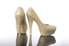 Pair of white pearls and lacy high pointed heels platform bridal shoes stock photo