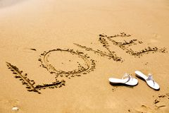 A pair of white sandals by inscription Love. On a sand at sunny day Royalty Free Stock Images