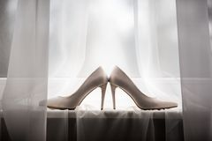 Pair of a white shoes, lying on the windowsill. stock images