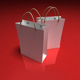 Pair of white shopping bags on a red background. 3D rendering of a pair of high quality white shopping bags against a shinny red background Royalty Free Stock Image