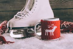 White skates with cup with knitted ornament and scarf. Pair of white skates with cup with knitted ornament and scarf Royalty Free Stock Image