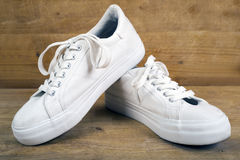 Pair of white sneakers with laces. On a wooden background stock image