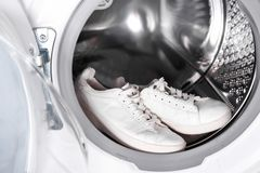 Pair of white sneakers in washing machine, Royalty Free Stock Photography
