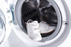 Pair of white sneakers in washing machine Royalty Free Stock Photography