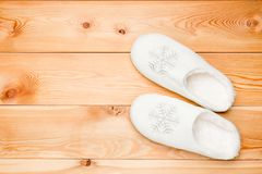 Pair of white warm slippers with snowflakes view from above on a. Wooden floor Stock Photos