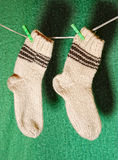 Pair of white wool socks. A pair of white wool socks on a clothesline in front of a green babckground Royalty Free Stock Photos