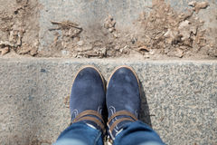 Pair of winter boots on female legs on stairs Royalty Free Stock Photo