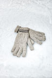 Pair of winter gloves lying in the snow Royalty Free Stock Images